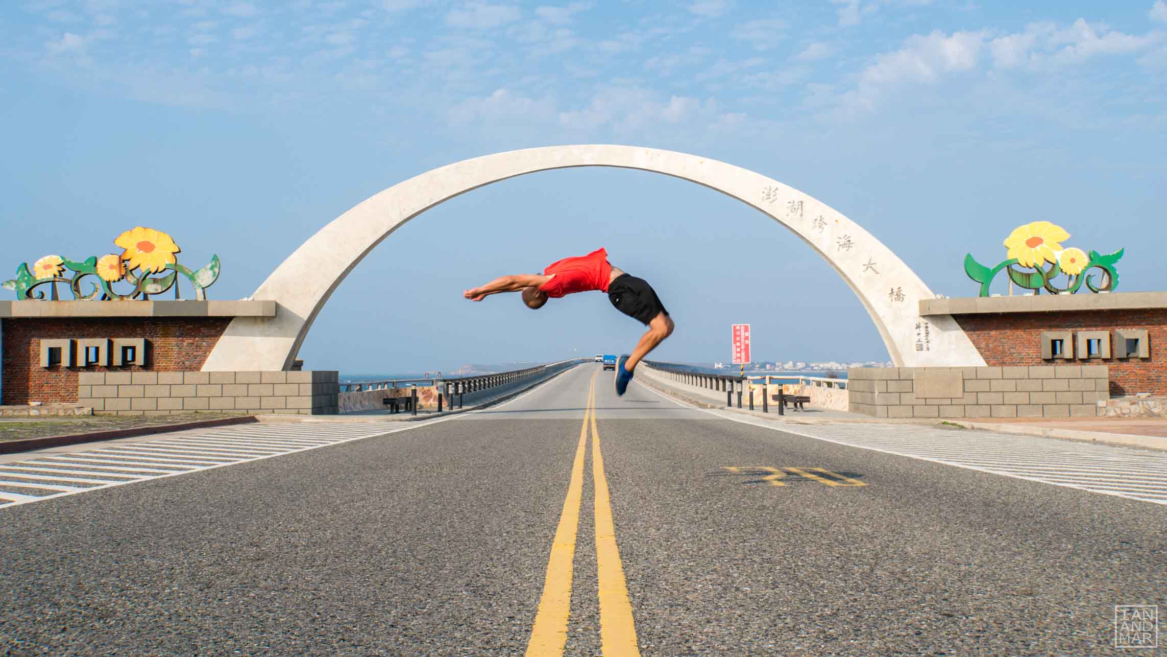 man doing a backflip in the middle of the road