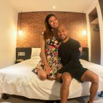 couple in bedroom with brick wall