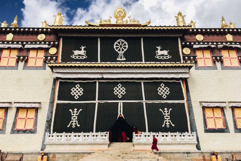 tibetan monk running to monastery door
