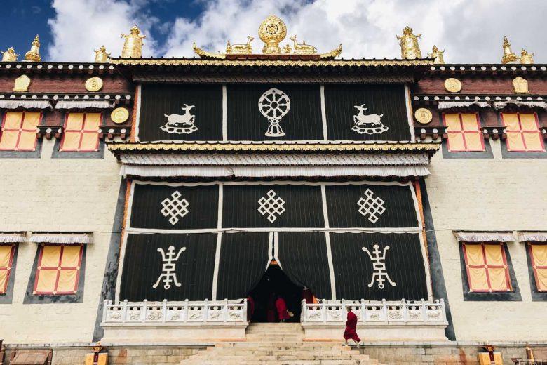 tibetan monk running to monastery door