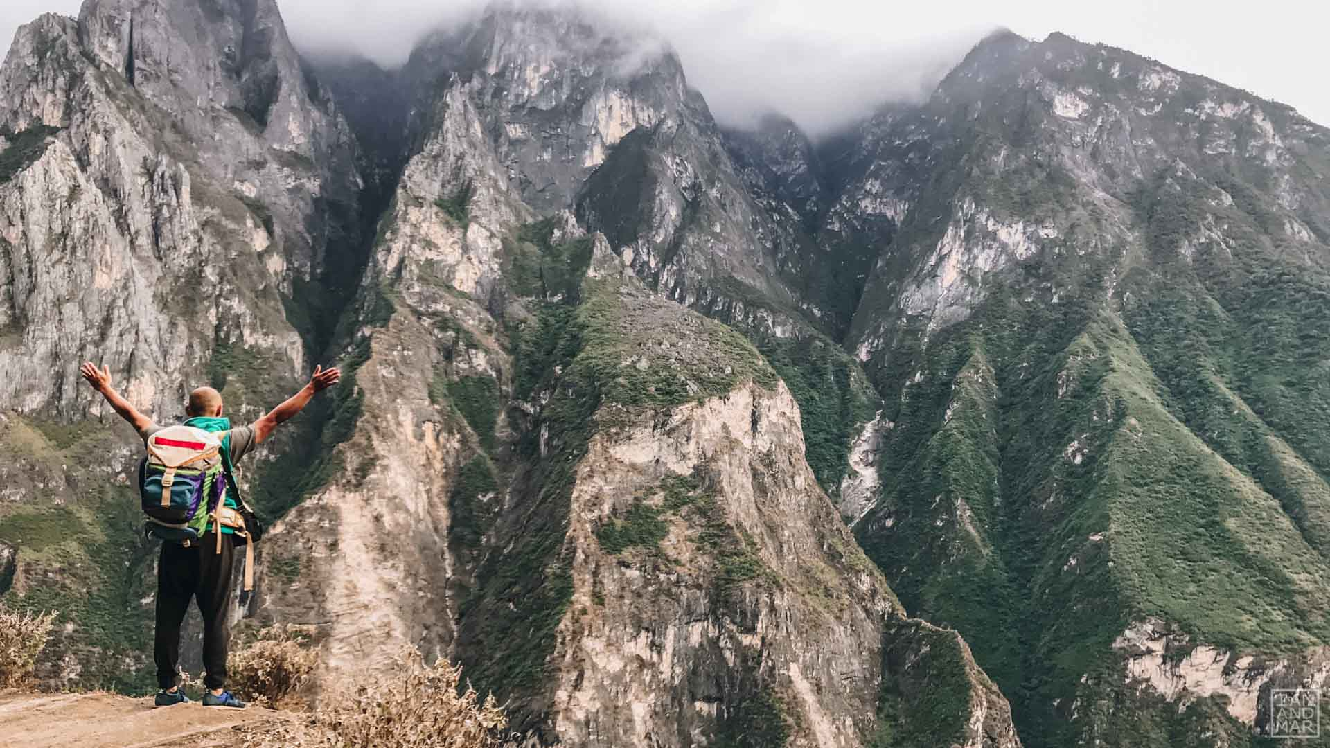 man with stretched arms in front of a mountain view