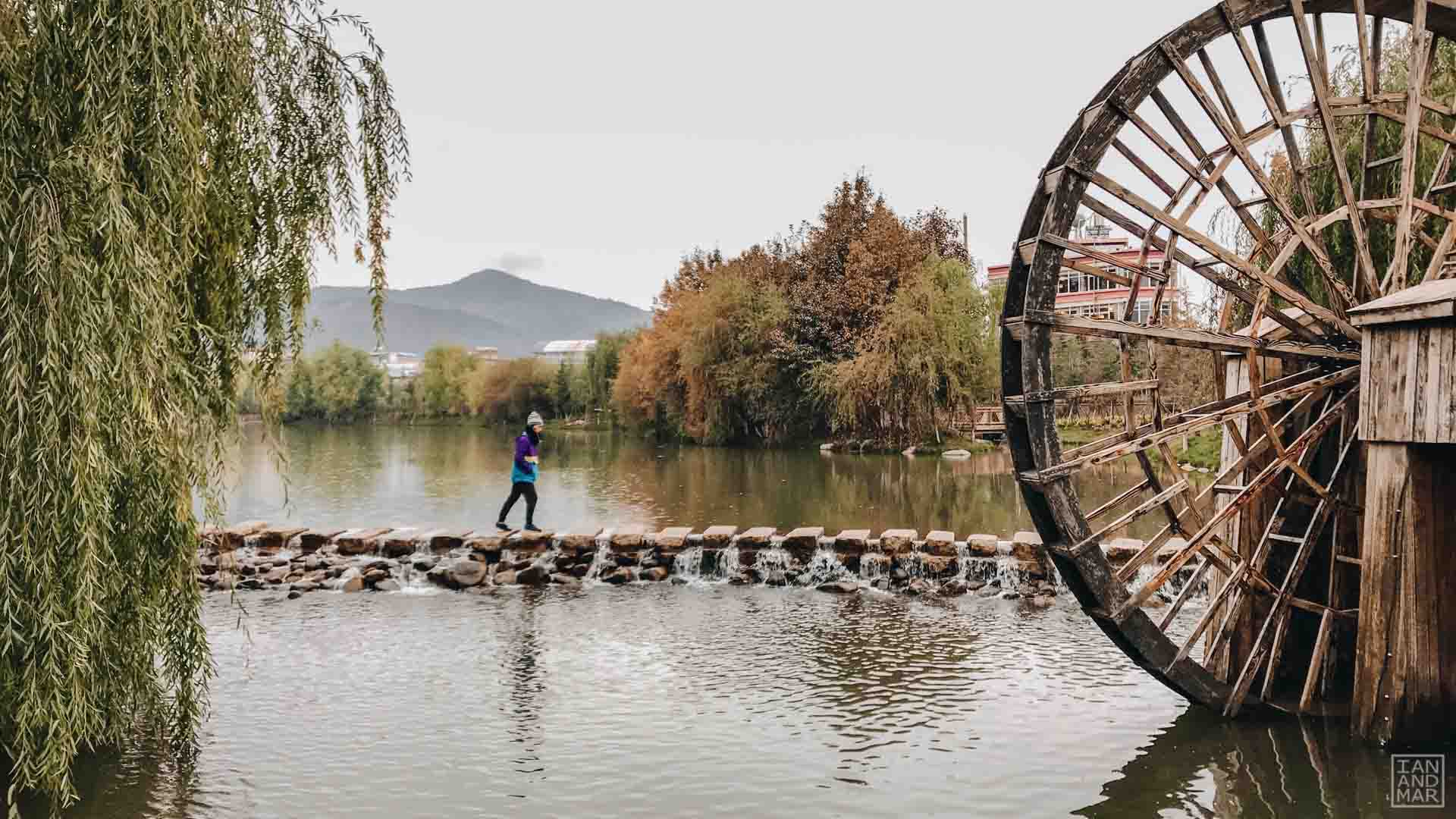 man crossing river with water wheel